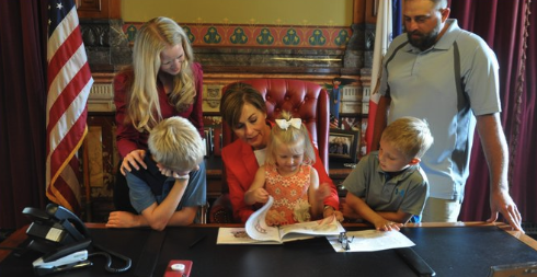 CRAEA staff member, Kelsey Baker, along with her family, with Gov. Kim Reynolds.